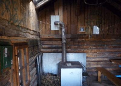 Le refuge St-Hubert et son balcon : vue de l'intérieur, avec le poêle